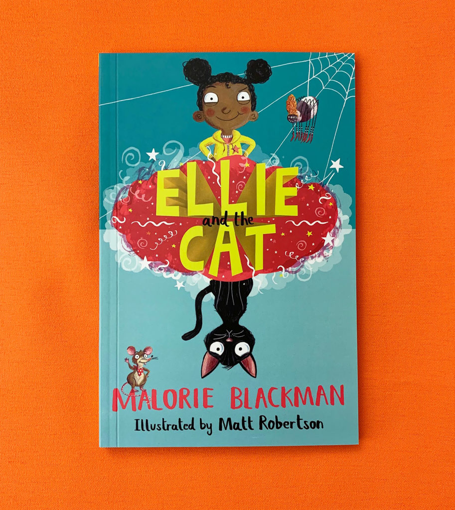Photo of the book Ellie and the Cat lying on an orange table. The book cover shows an illustration of a young girl, a cat, a mouse and a spider with the title written out in the centre,