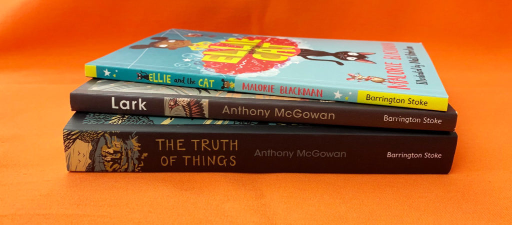 January New Titles | A photograph showing a stack of books on an orange table. The photo shows the spines of Ellie and the Cat by Malorie Blackman, Lark by Anthony McGowan, The Truth of Things by Anthony McGowan