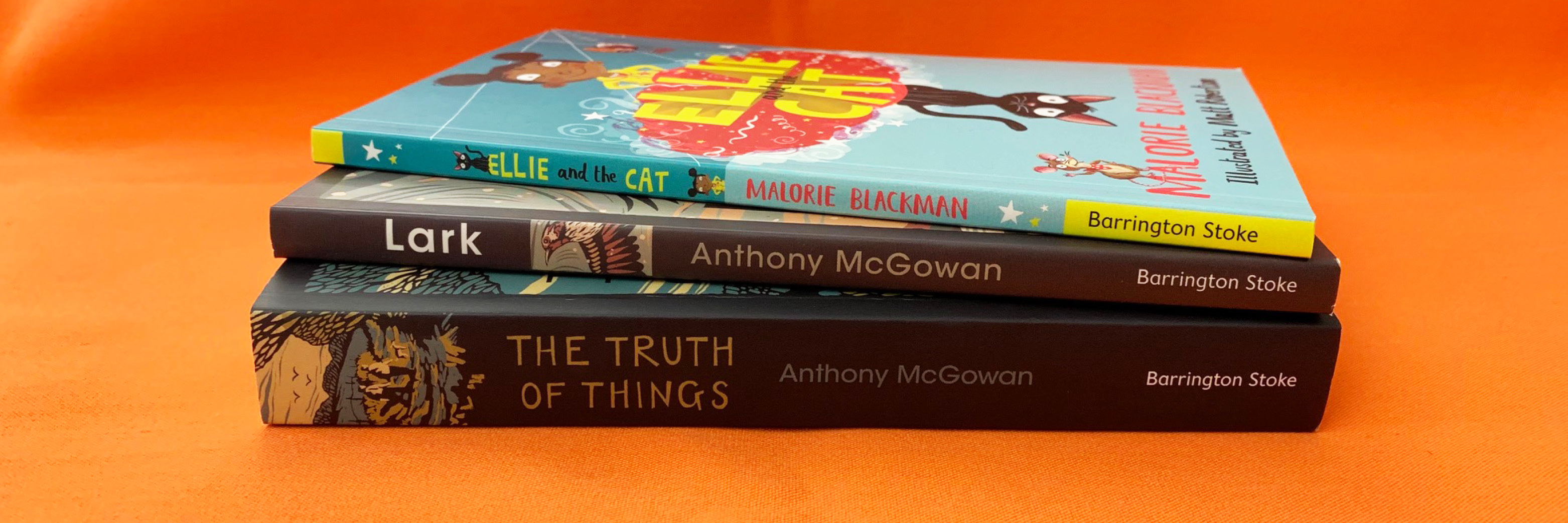 A photograph showing a stack of books on an orange table. The photo shows the spines of Ellie and the Cat by Malorie Blackman, Lark by Anthony McGowan, The Truth of Things by Anthony McGowan
