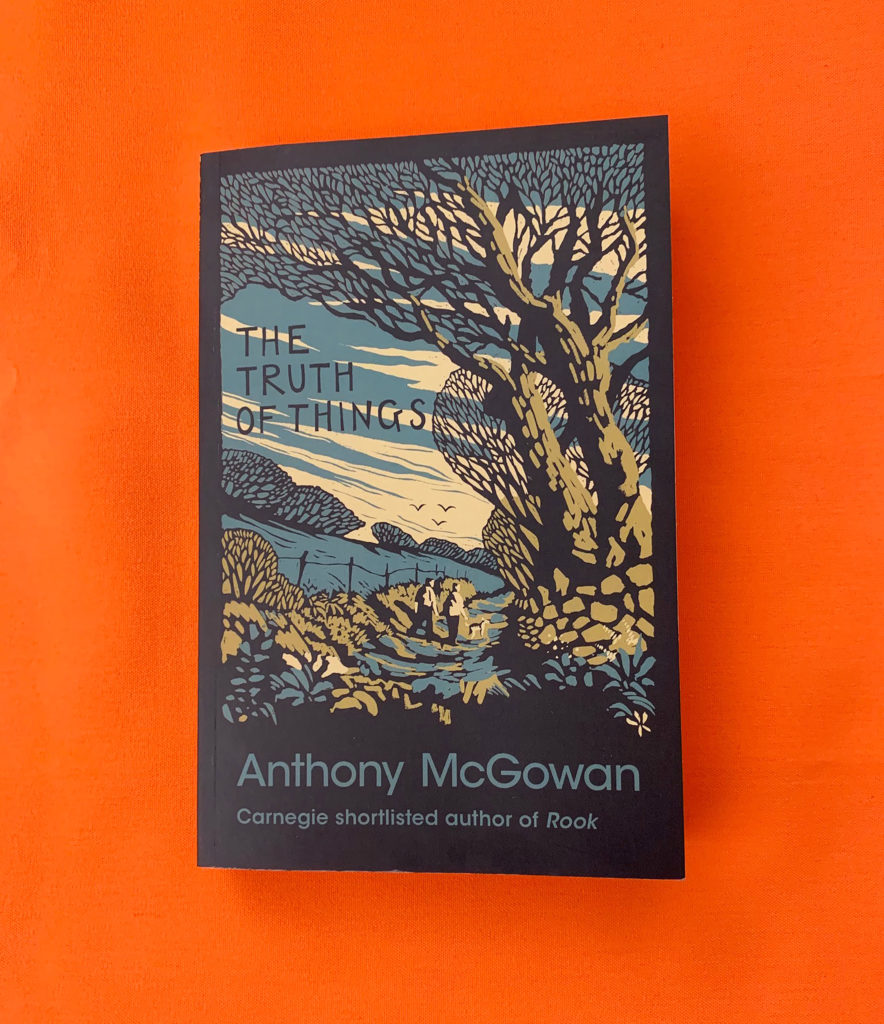 """A photo of the book The Truth of Things lying on an orange table. The cover shows an illustration in hues of blue and green of a countryside scene. It shows two boys walking a country lane with their dog. The title is written above the boys and below them """"Anthony McGowan, Carnegie Shortlisted author of Rook"""" is written."""