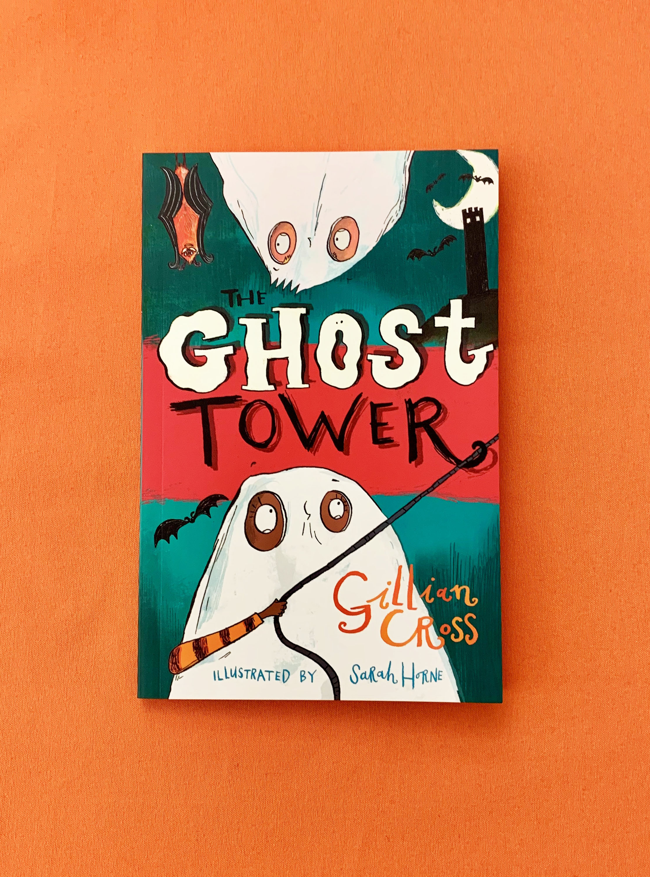 The book The Ghost Tower lying on an orange table