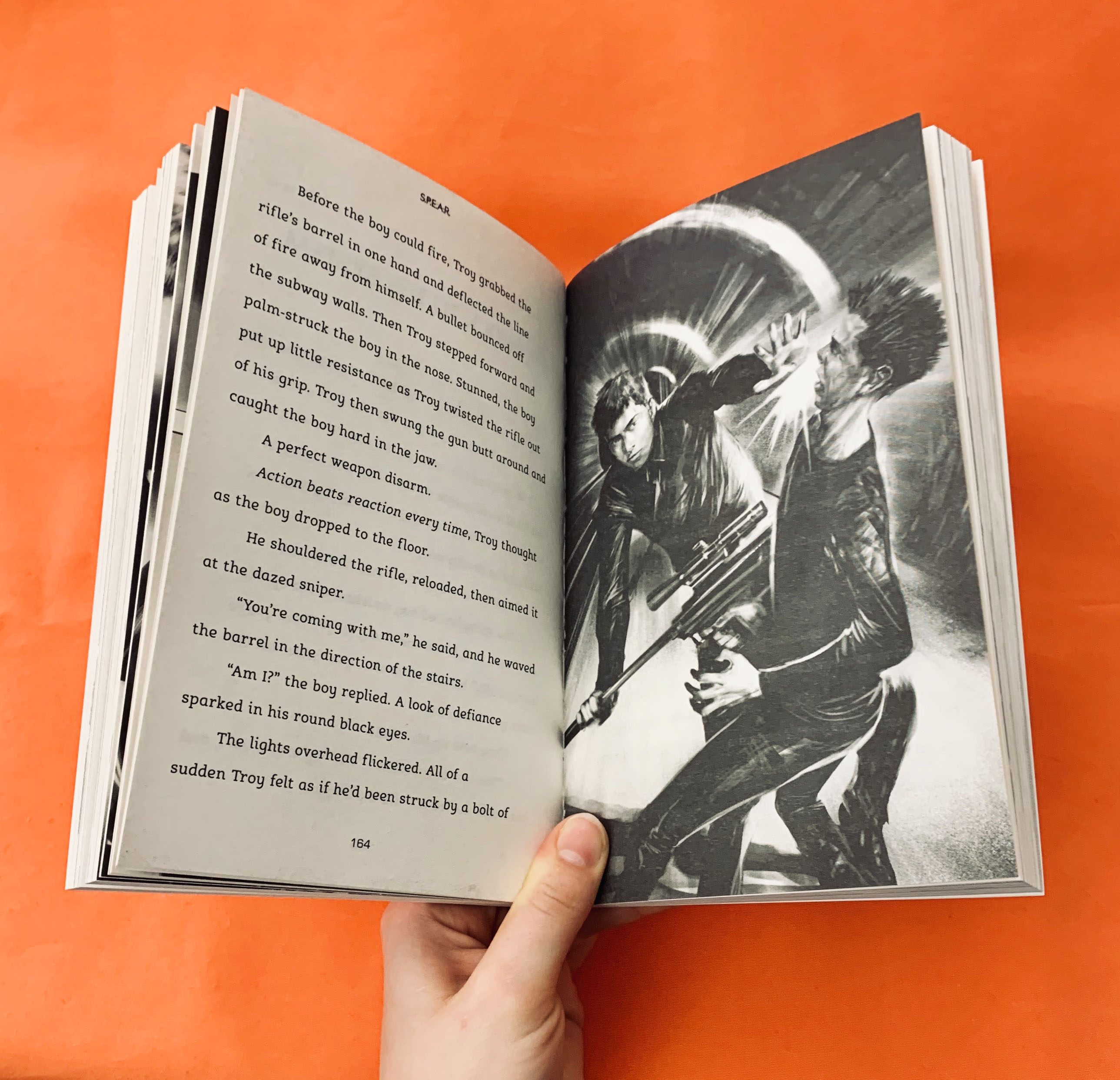 An image of the book S.P.E.A.R opened to a page with an illustration of two teenagers caught in a nail-biting fight