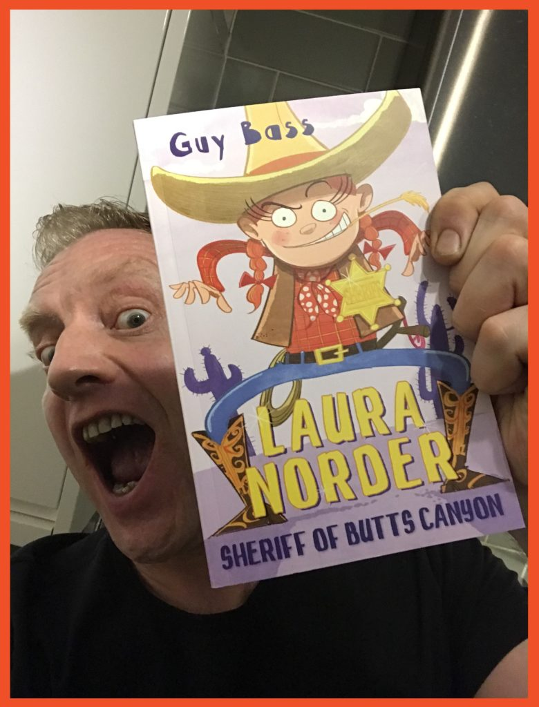 Photograph of Stave May holding the book Laura Norder and pulling a funny face