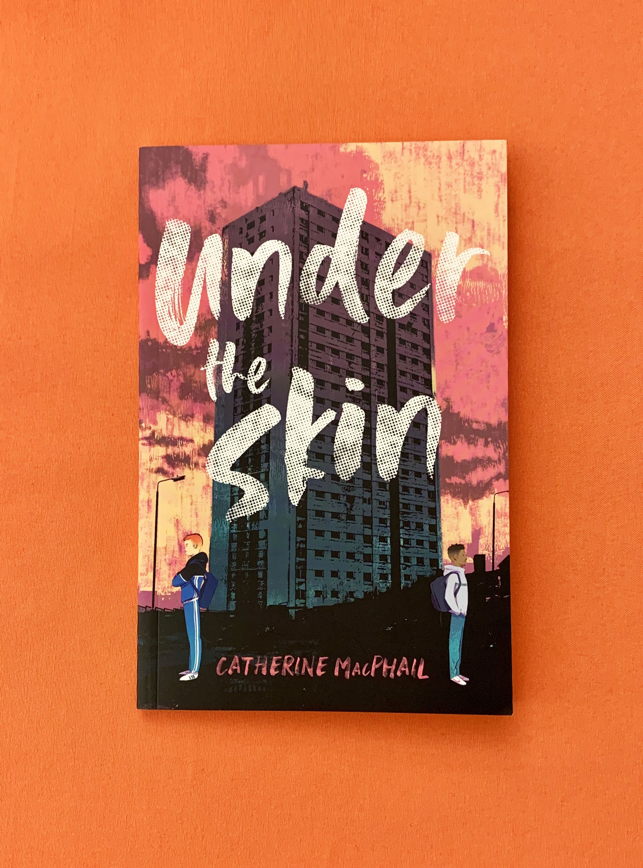 Image of the book Under the Skin lying on an orange table