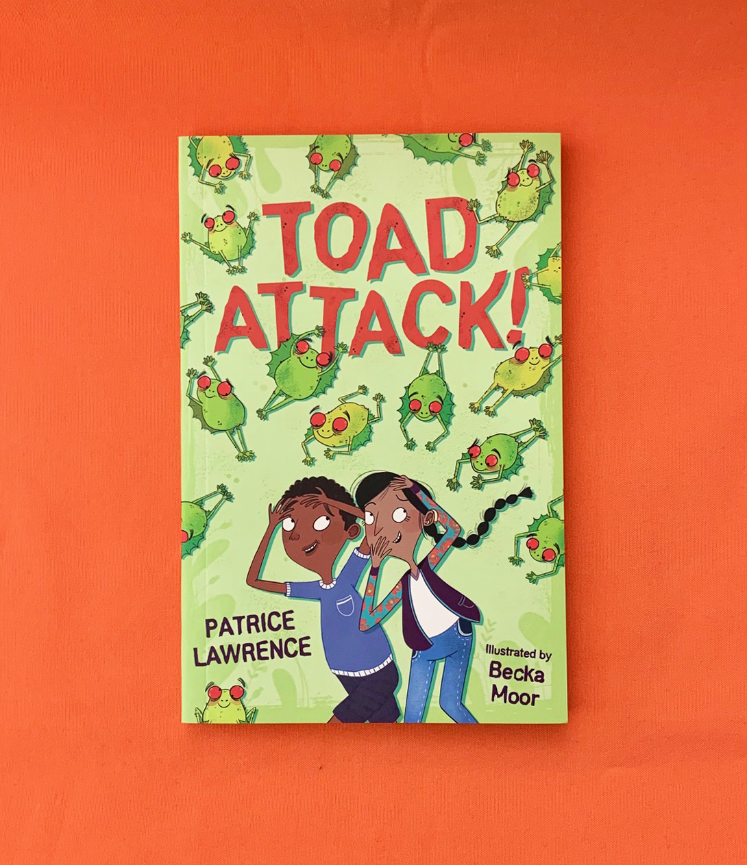A photograph of TOAD ATTACK by Patrice Lawrence lying on an orange table