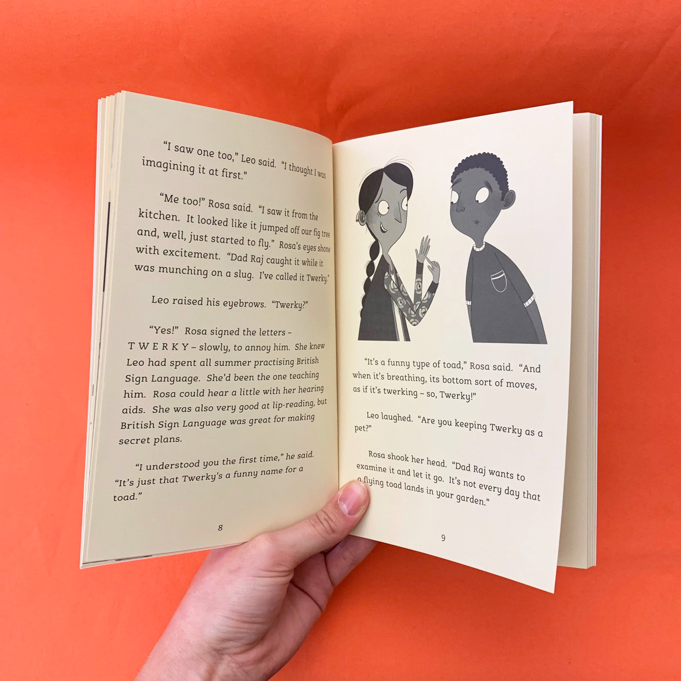 A photograph of a page spread from Toad Attack, featuring an illustration of Rosa signing
