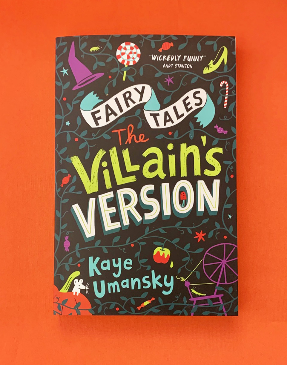 A photograph of the book FAIRY TALES; THE VILLAIN'S VERSION lying on an orange table