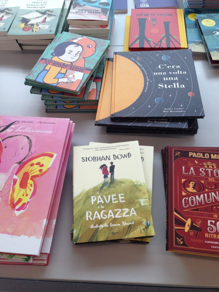 A photograph of a table display of books showing a stack of the Italian edition of The Pavee and the Buffer Girl